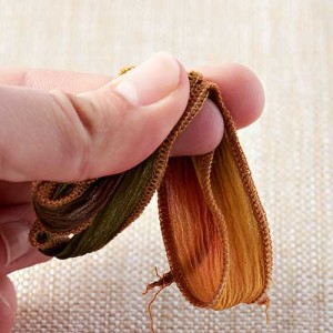 Silk Ribbon Tassel Earrings - Step 1: Cut silk ribbon in half. Take one half and fold in half. Fold again and again for a total of three half folds.