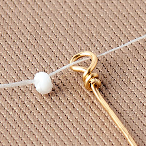 Step Two: Knot a bead to the end of the thread. Feed the thread through wire loop.