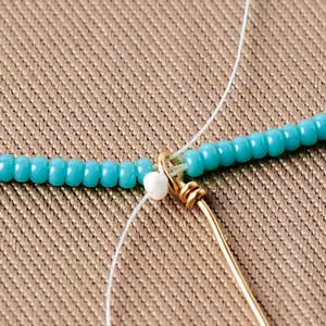 Step Six: String on beads and thread back through the beads while skipping the last bead. Then go back through the wire loop.